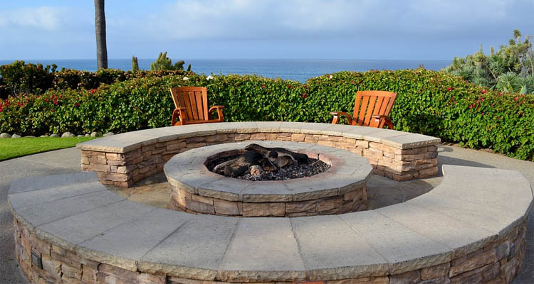 Custom fire pit made from stone with seating.
